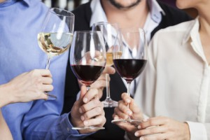 Cropped image of male and female friends toasting wine glasses in winery